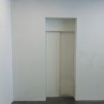 weiße Aufzugstür in weißer Wand